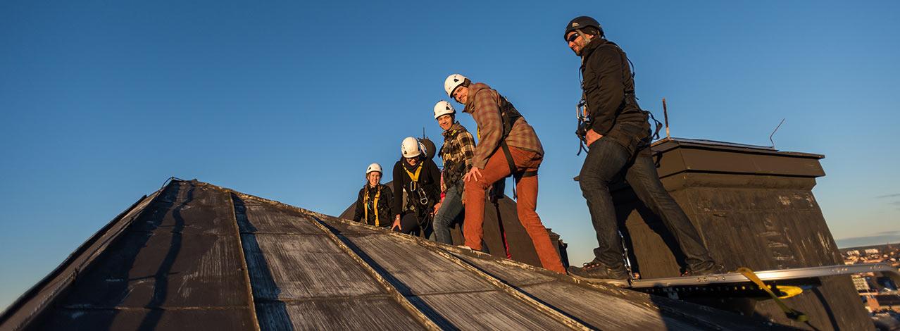 Fem personer går på ett tak.